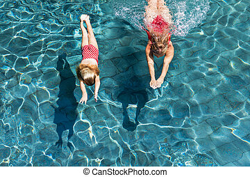 Child with mother dive underwater in swimming pool