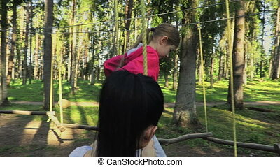 Child with mother in a adventure playground