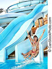 Child with mother on water slide at aquapark. Summer holiday...