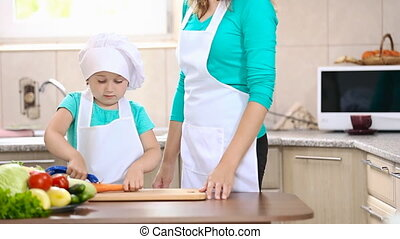 Child with mum clean carrots