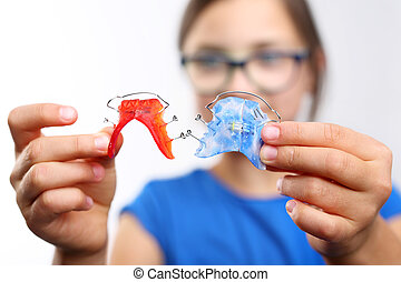 Pretty girl with colored orthodontic appliance .