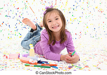 Adorable 6 year old child laying on paint splattered floor with bottles of spilled paint.