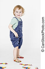 child with painted feet holding trousers up. studio shot in ...