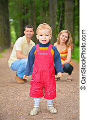 child with parents in park
