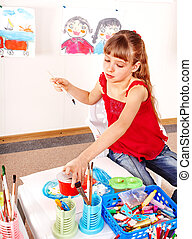 Child with picture and brush in playroom.