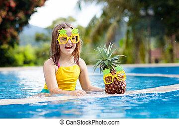 Child with pineapple in swimming pool. Kids swim.