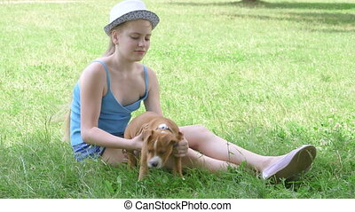 Child with puppy dog on green lawn in summer day