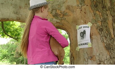 Child with puppy reads the lost pet sign on tree trunk