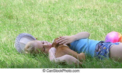 Child with puppy resting in shade on grass in summer day