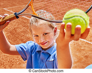 Child with racket and ball on tennis court - Child girl with...