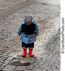 Child with raincoat has fun in the rain