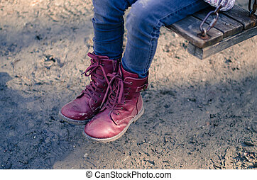 child with red shoes in swing