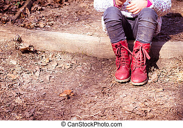 child with red shoes sitting and waiting