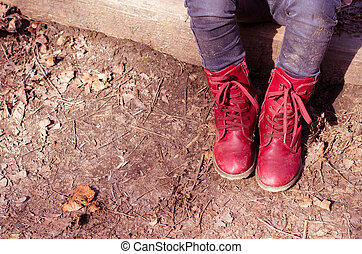 child with red shoes sitting