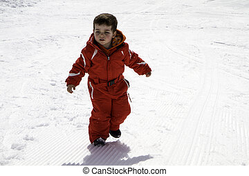 child with red ski suit in the snow