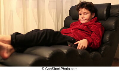 Child with remote controller lying on a sofa