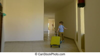 Child with rolling bag running along the hotel corridor