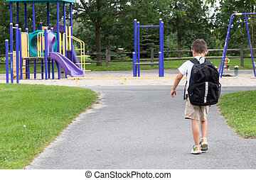 Child with school backpack and book walking in the park