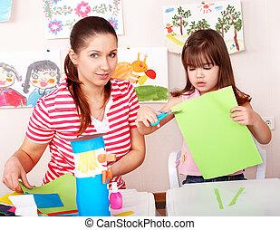 Child with scissors cut paper in play room. Preschool.