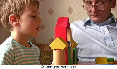child with senior built toy house