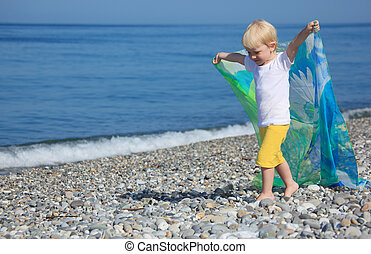 child with shawl goes on pebble beach