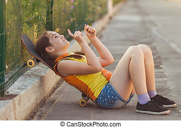 child with skateboard sitting on th