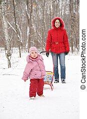 child with sled and mother in park at winter 2