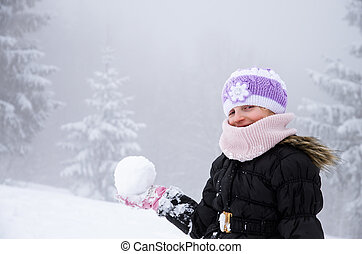 child with snowball in winter forest