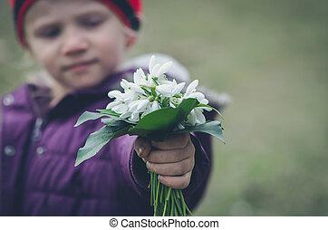 child with snowdrop bouquet
