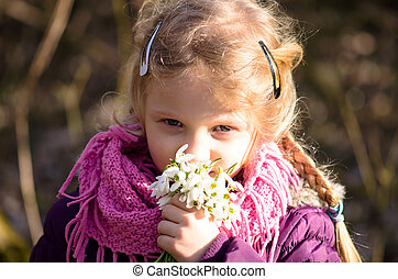 child with snowdrop flowers