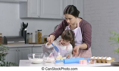 Child with special needs baking with mother