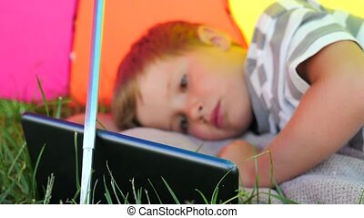 Child with tablet lying on green grass under sun umbrella. Summer vacation concept.