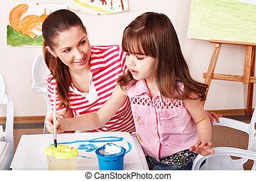 Child with teacher draw paints in play room. Preschooler.