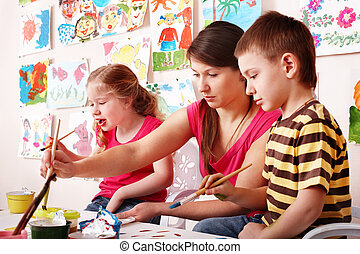 Child with teacher draw paints in play room. Preschool..
