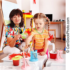 Child with teacher draw paints in playroom.