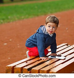 child with the tablet on bench