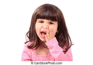 Cute young four year old child holding her cheek with a toothache
