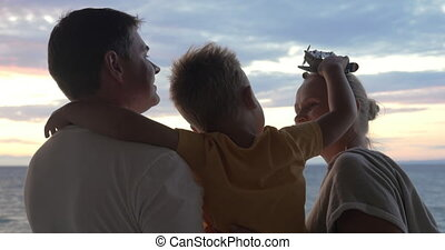 Child with toy plane and parents outdoor