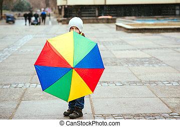 Cute little boy walking the street on rainy day.