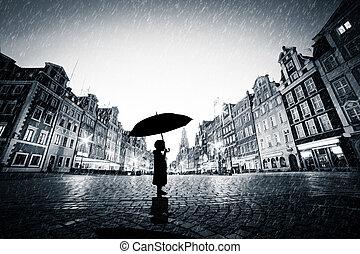 Child with umbrella standing alone on cobblestone old town in rain