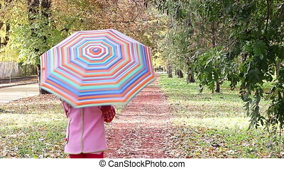 child with umbrella walking in park autumn season