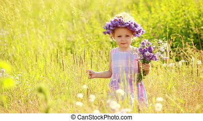 Child with violet flowers in the pa