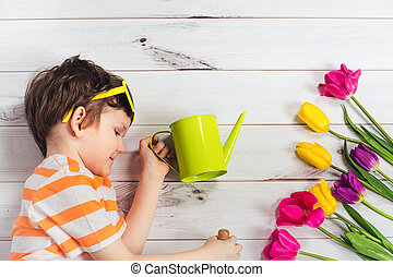 Child with watering can and tulips lying on a light wooden floor.