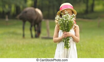 Child with wild flowers in their hands sniffs them. Slow motion