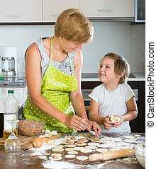 Child with woman making meat dumplings - Happy child with...