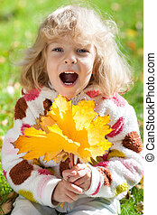 Child with yellow maple leaves