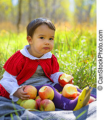 child withf red apples sitting on leaves in autumn park
