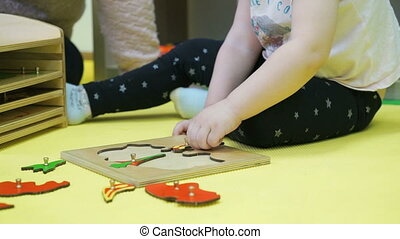 Child works with puzzles sitting on the floor at a nursery...