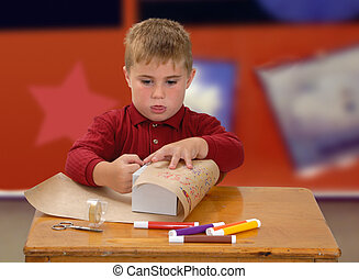 Child Wrapping Gift - Boy at school making gift paper and ...