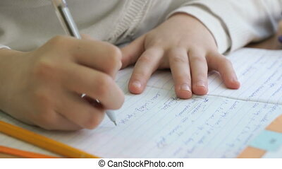 Child writes the text in a workbook with a pen